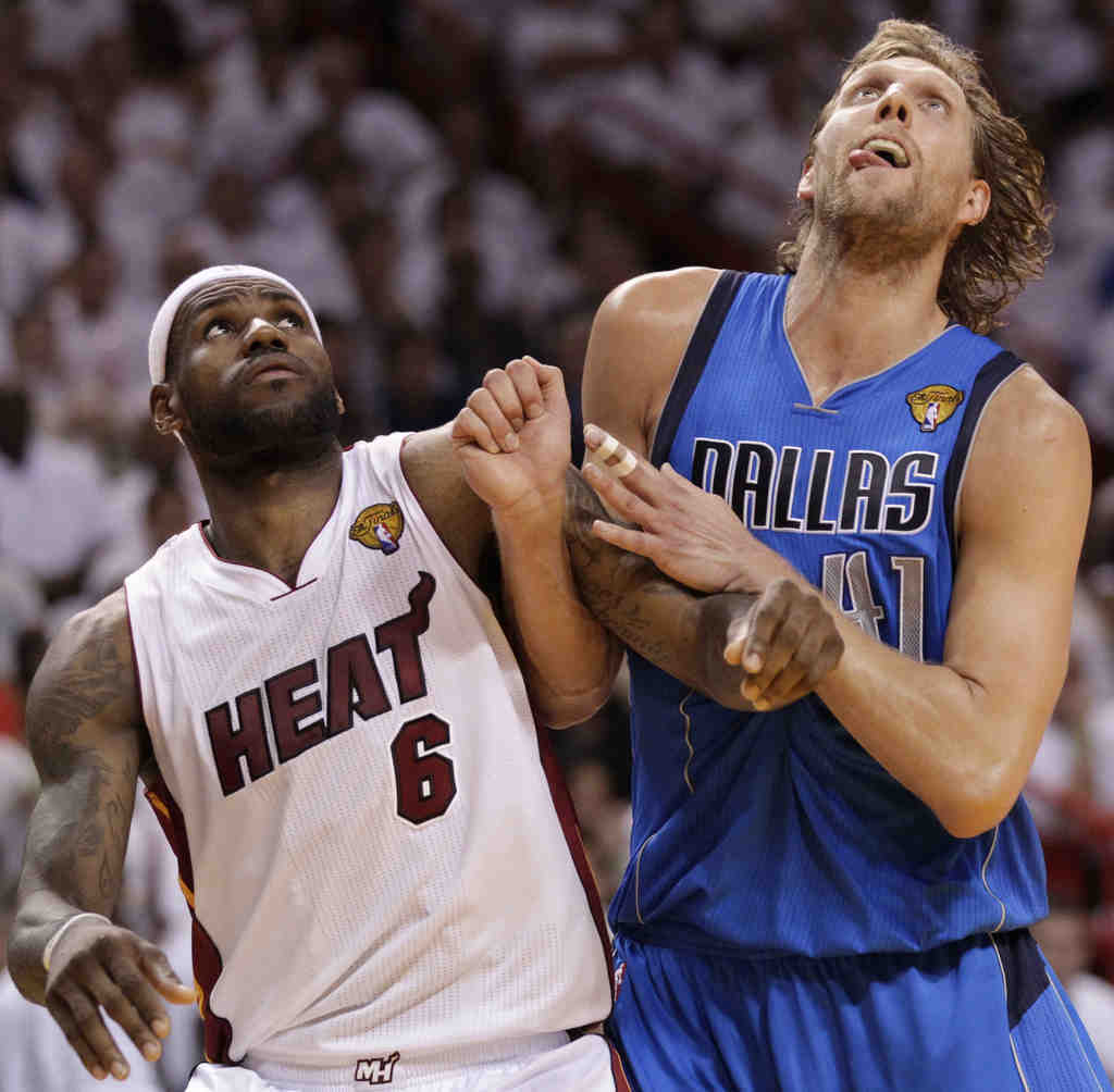 LeBron James and Dirk Nowitzki (right) battle. A bench-clearing altercation in the first half resulted in three technical fouls.