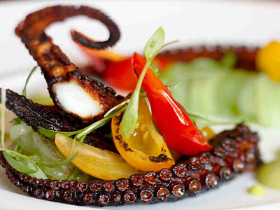 Octopus with charred tomatoes, tomatillo-avocado salsa, and cucumber at Mica. (David M Warren / Staff Photographer)
