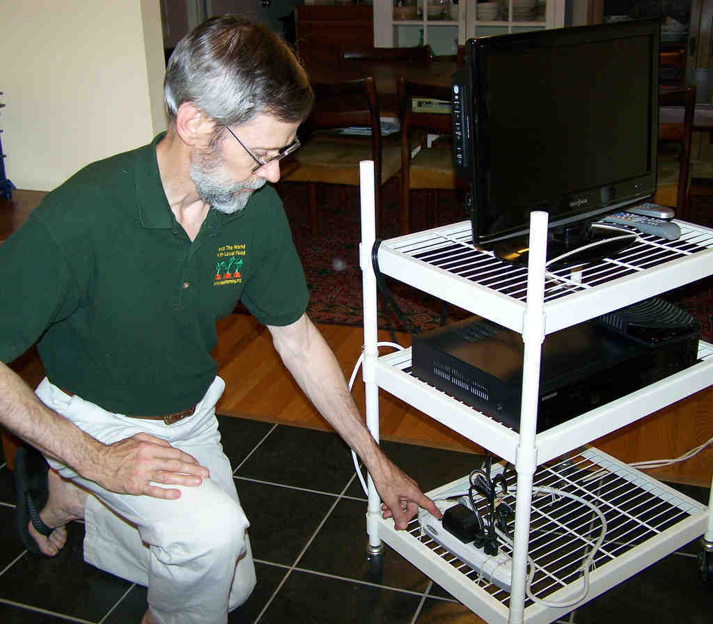 Don Kennedy with his TV-cable box-DVD player/VCR setup on a movable cart in his home in Swarthmore. To prevent the cable box from using power when the TV is off, he turns off everything using the power strip.