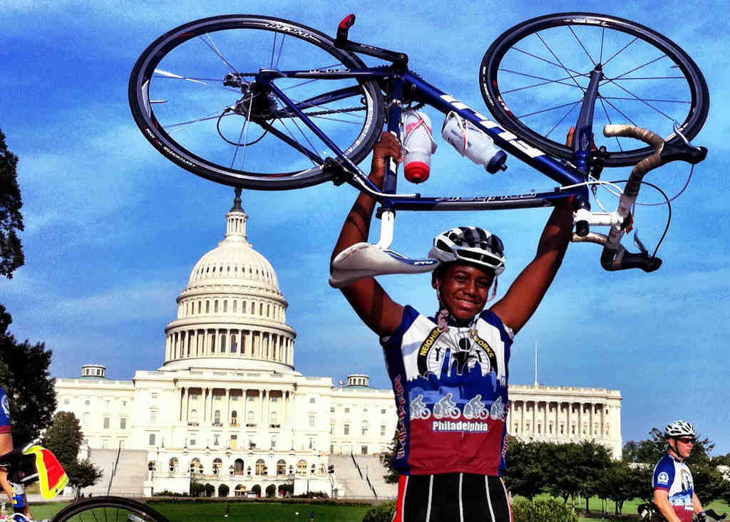 Mark Edens of the Neighborhood Bike Works team lifts his bike in triumph in front of the Capitol after riding nearly 200 miles from West Philly.
