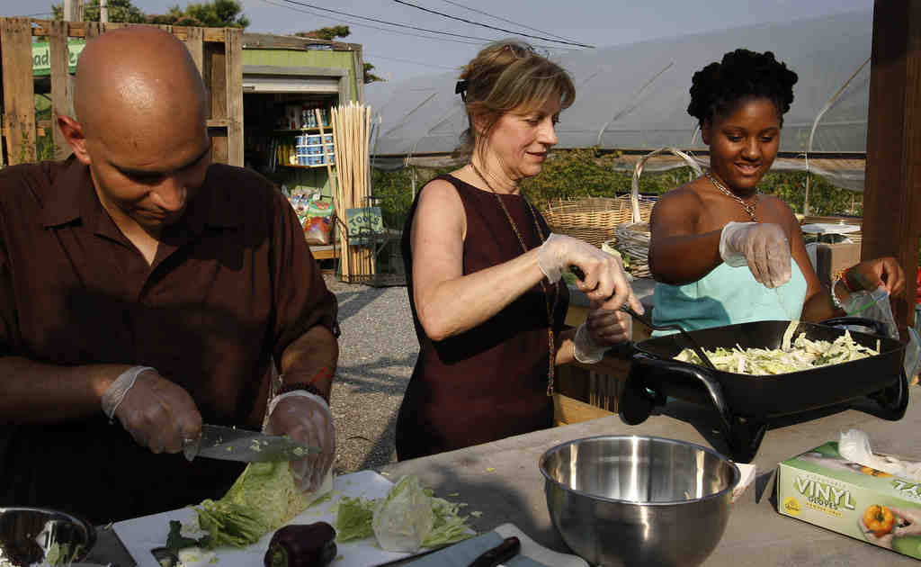 Frank Abruzzo chops, Christine Persicketti stirs, and Simran James of Penn State Extension adds ginger to Garlic Ginger Cabbage in a cooking demonstration at Greensgrow Farm in Kensington. (Michael S. Wirtz / Staff Photographer)