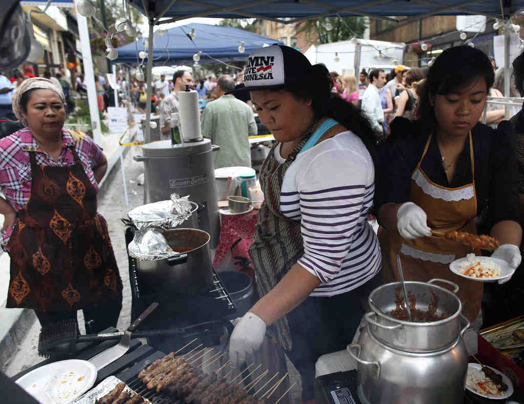 Maylia Widjojo (second from left) grills skewers of lamb and chicken at Hardena Grill, staffed by her mother, Ena (far left), and sister Diana. The Night Market was one of series run in different Philadelphia neighborhoods by the Food Trust.