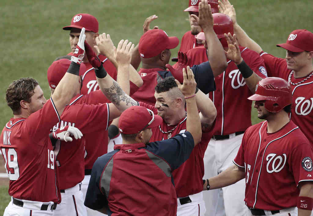 Jonny Gomes (center) is Nationals hero after being hit by pitch to walk in the winning run.