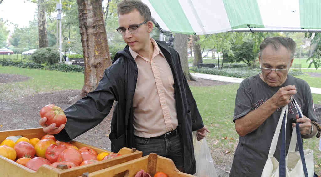 Bench Ansfield, a Philly Food Bucks user, picks up a tomato at Clark Park in West Philadelphia. The pilot effort provides $2 in vouchers for every $5 spent on produce at Food Trust markets.