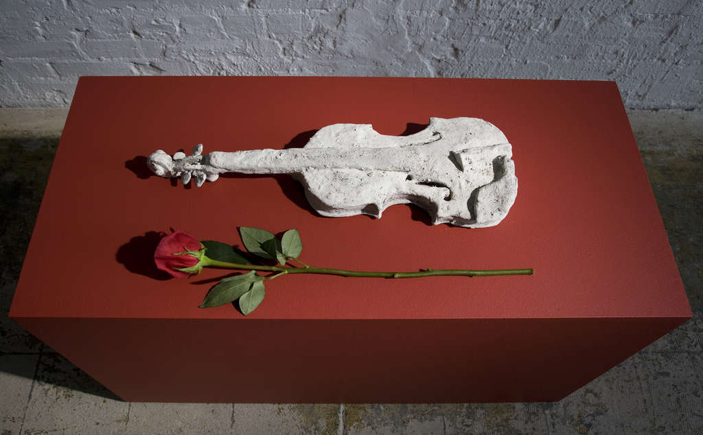 """""""The Sweetness of Music,"""" above, made by Laurie Anderson of mud, clay, and the ashes of her terrier Lolabelle; the violin is Anderson´s signature instrument. Left, """"Lola- belle in the Bardo,"""" one of a series of 10 huge charcoal-on- paper drawings. The exhibit, """"Forty-Nine Days in the Bardo,"""" also includes a half-dozen tiny videos projected onto clay figures of people in a dark room."""