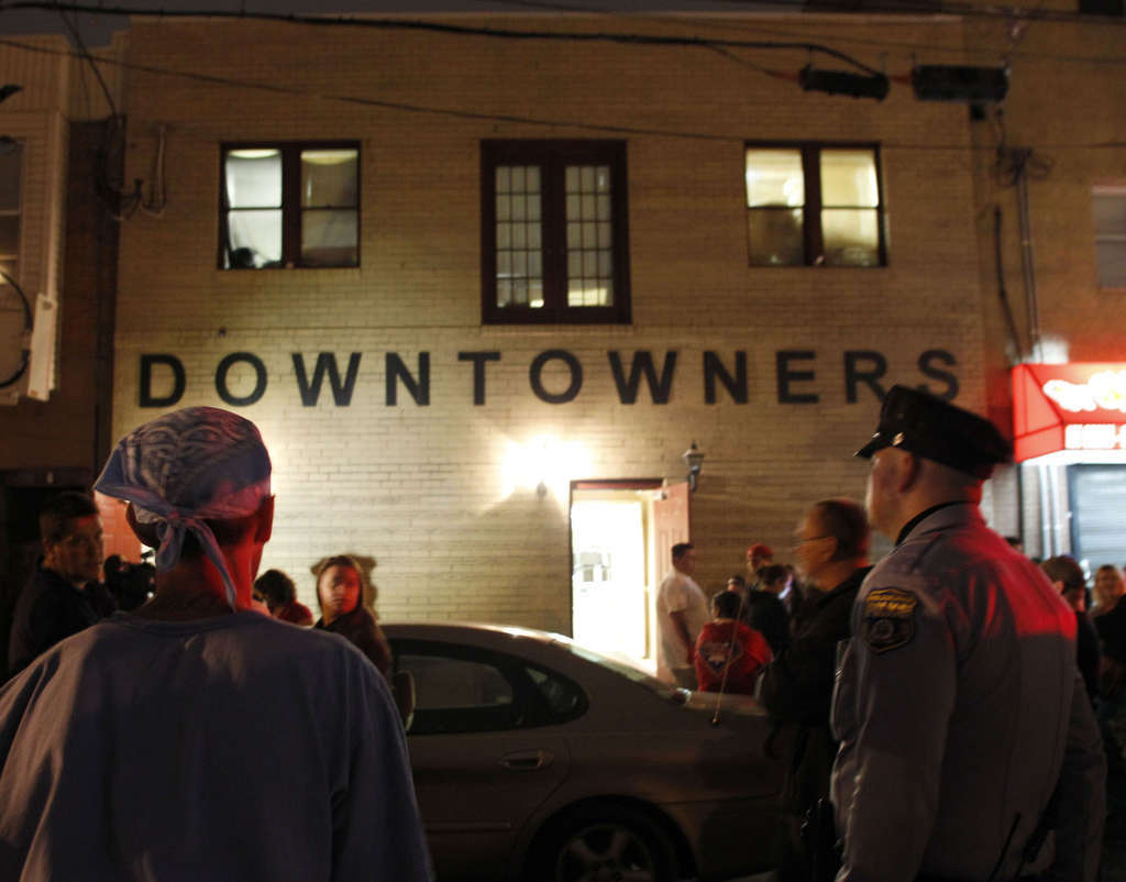 A police officer and others watching the prostitution raid Tuesday at the South Philadelphia clubhouse of the Mummers´ Downtowners Fancy Brigade. Thirteen people were arrested.