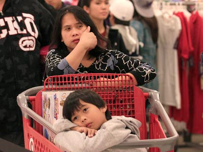 Meda Palines and her son Darren, 6, wait in line for the checkout at aTarget Store in Colma, Calif., Friday, Nov. 25, 2011. The American holiday shopping season began in earnest Friday as stores opened their doors at midnight _ a few hours earlier than they normally do on the most anticipated shopping day of the year. (AP Photo/Jeff Chiu)