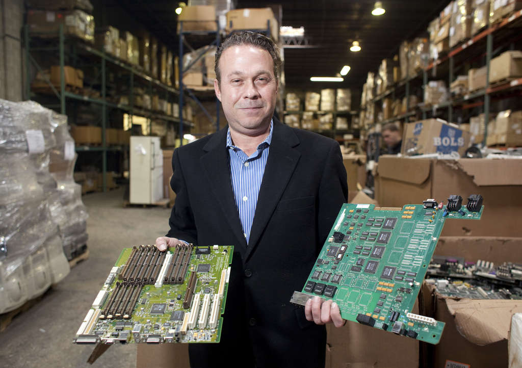At eForce Compliance on Grays Ferry Avenue, managing director Charles Nygard holds circuit boards. The facility dismantles electronics so recoverable parts can be reused.
