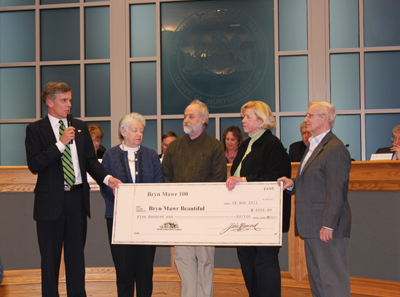 (left to right) Before the debate over the contract, Commissioner Scott Zelov, Bobbie McElroy and Hank Wilson of Bryn Mawr Beautiful, and Bryn Mawr Business Association Kathy Bogosian and businessman Dave Fish of John Fish & Son, received a check of $500 fundraised for Bryn Mawr Beautiful.