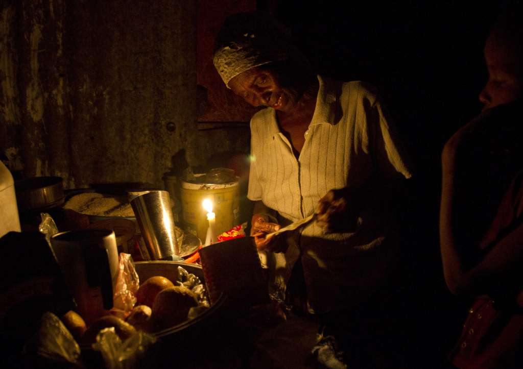 A woman prepares food by candlelight in Haiti´s capital, Port-au-Prince, where many are still without electricity and basic services two years after the January 2010 earthquake.