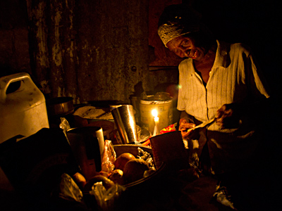 A woman prepares food by candlelight in Haiti´s capital, Port-au-Prince, where many are still without electricity and basic services two years after the January 2010 earthquake. (Dieu Nalio Chery / Associated Press)