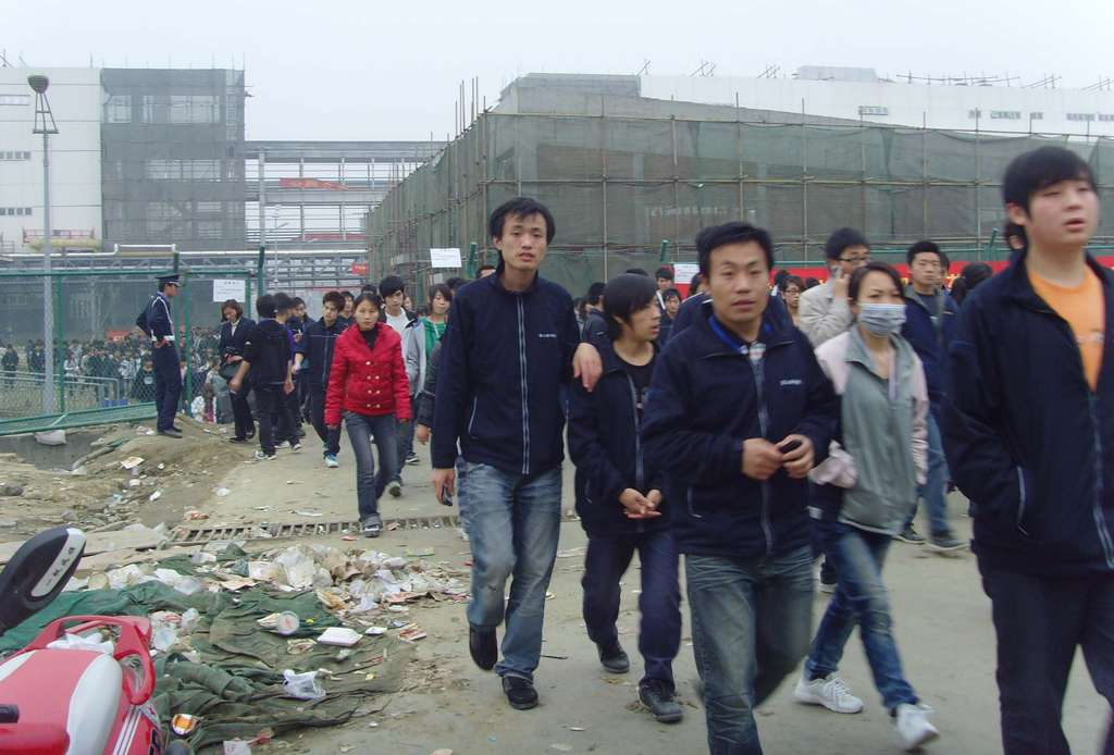 Workers leave a massive Foxconn plant under construction last year. It employs about 430,000 people in Shenzhen, China, and is accused of using underage labor, forcing long hours, and other bad practices.