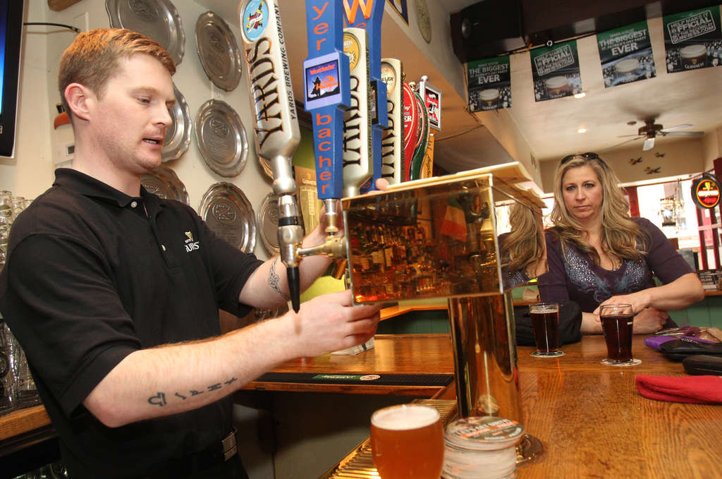 Bartender John Clarke draws a beer at the Bards as Kristin Lisi watches. CHARLES FOX / Staff Photographer