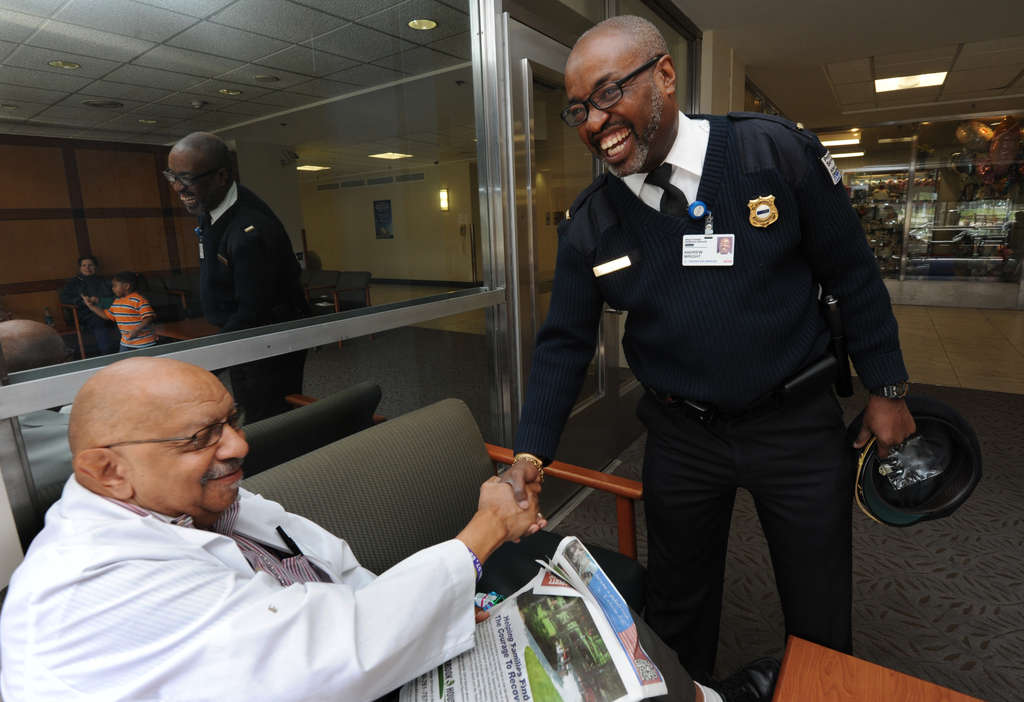 At Einstein, security supervisor Andy Wright (right) greets lab tech Hobson Gross. Wright gives $1,500 a year to the foundation. APRIL SAUL / Staff Photographer