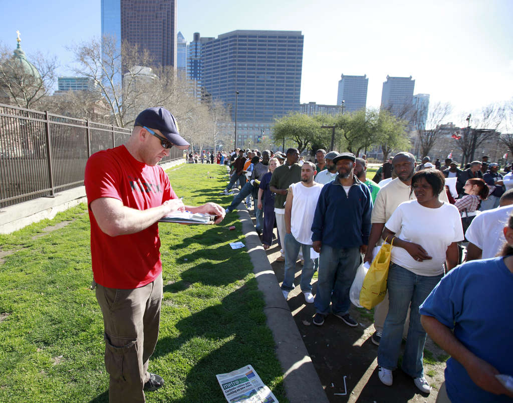 Homeless advocate Adam Bruckner writes checks for $13.50 to help people obtain a state ID. On Monday, he was at it again on Ben Franklin Parkway in front of the Family Court building. DAVID SWANSON / Staff Photographer