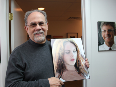 Narberth´s Richard McKnight holds a portrait of his daughter Amanda he painted on the iPad application, ArtRage. His iPad portraits cover the walls of Dr. Arnold Weinberg´s Narberth Chiropractic Center on North Essex Avenue.