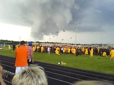 Absegami High School graduates throw their caps into the air with ominous storm clouds as a backdrop. (YouTube)