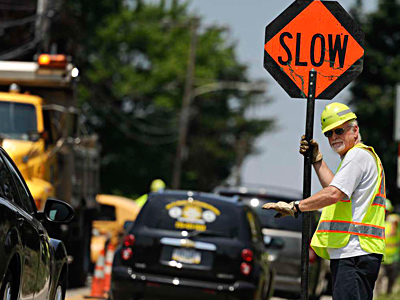 PennDot worker Mike Bryan endures the heat while directing traffic along Crooked Lane in Bridgeport. RON TARVER / Staff Photographer