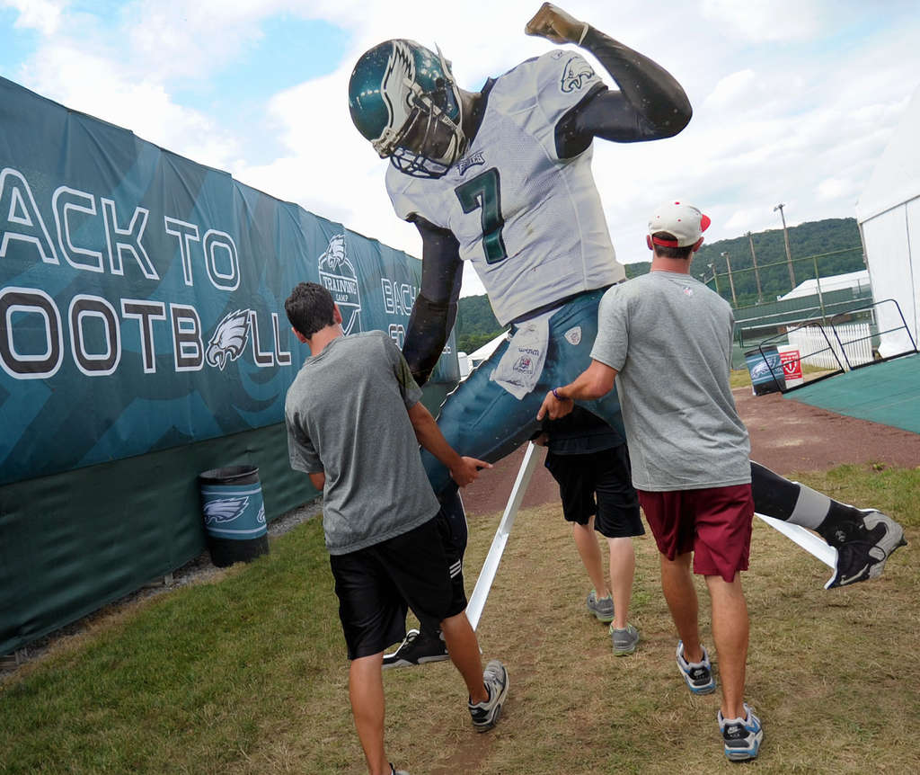 A larger-than-life cutout of Michael Vick is carried onto the field at Lehigh University by Eagles interns Sean Gale (left) and Kyle Heckelman.