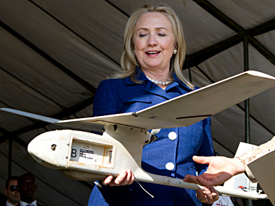 Secretary of State Clinton, in Uganda, said she hopes drones like the one she holds will be able to locate warlords in jungles. JACQUELYN MARTIN / AP, Pool