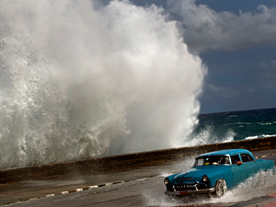 A driver maneuvers along a wet road as a wave crashes against the Malecon in Havana, Cuba, on Thursday after Hurricane Sandy blasted across eastern Cuba. RAMON ESPINOSA / Associated Press
