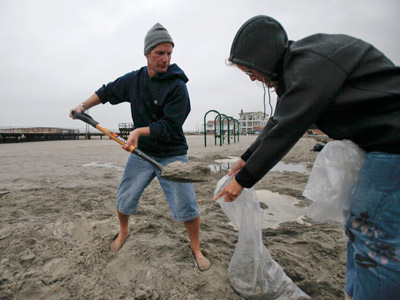 Terry Junker, left, and Nancy Lisowski fill sandbags at the beach in Ventnor on Sunday to be used at their home in preparation for Hurricane Sandy. (AP Photo/ Joseph Kaczmarek)