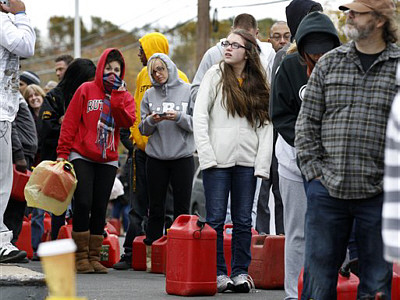 As temperatures begin to drop, people wait in line to fill containers with gas at a Shell gasoline filling station Thursday, Nov. 1, 2012, in Keyport, N.J.