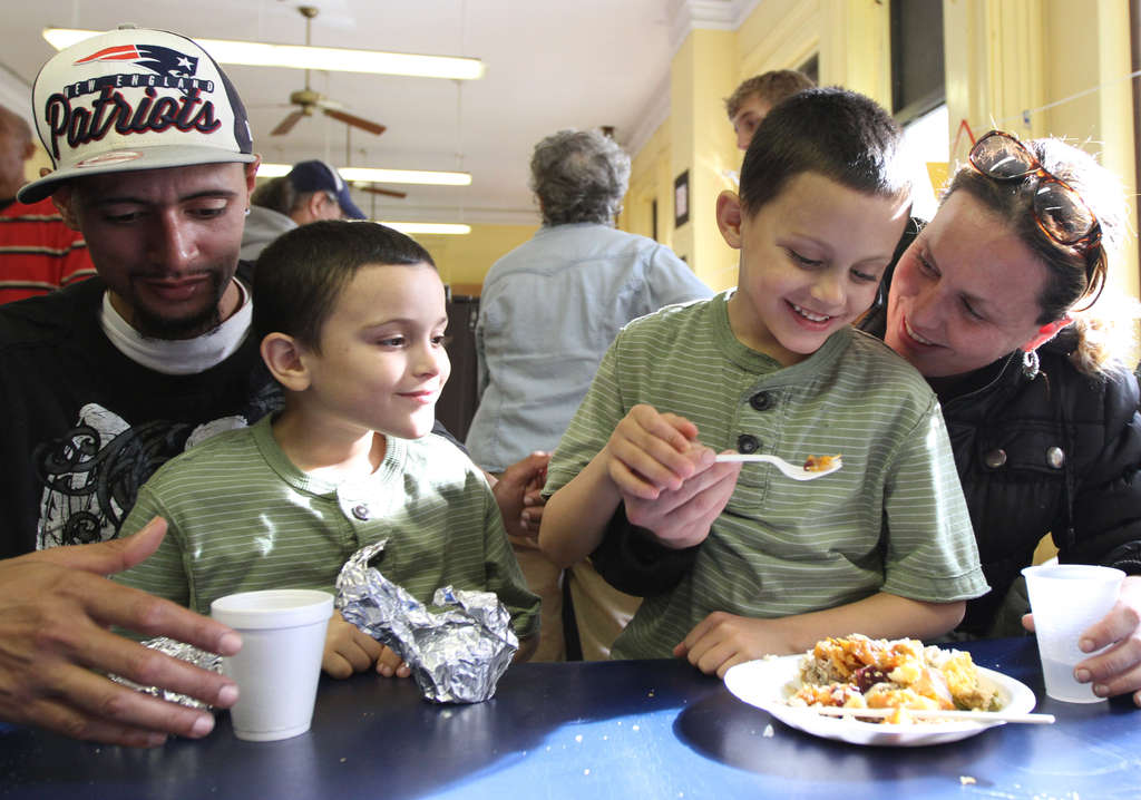 Ramon Torres, his twin sons Miguel (left) and Julio, and wife Tanya enjoy a Thanksgiving meal on Sunday at St. Vincent´s, which partnered with Faith Chapel. DAVID SWANSON / Staff Photographer