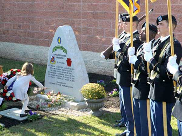 "On Veterans Day 2012, the 111th Infantry Regiment dedicated a ""Fallen Warriors"" monument to its eight dead from the Iraq war. Family members and relatives of the fallen soldiers lay flowers at the memorial during the ceremony at the National Guard Armory in Plymouth Meeting. (CHARLES FOX / Staff Photographer )"