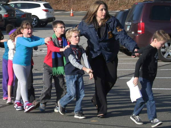 In this photo provided by the Newtown Bee, Connecticut State Police lead a line of children from the Sandy Hook Elementary School in Newtown, Conn. on Friday, Dec. 14, 2012 after a shooting at the school. (AP Photo/Newtown Bee, Shannon Hicks)