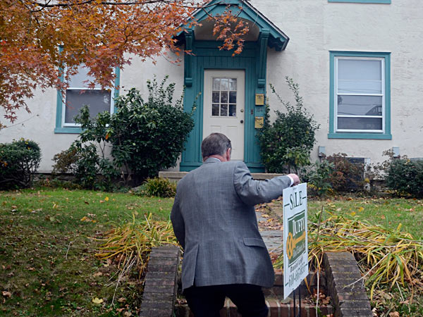 John Duffy puts up a for-sale sign at one of his listings in Narberth. TOM GRALISH / Staff Photographer