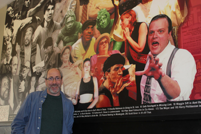 Seth Rozin, 47, InterAct's producing artistic director, standing in the Adrienne Theater next to a collage of stills from 15 years worth of the company's plays. (Josh Fernandez / Philly.com)