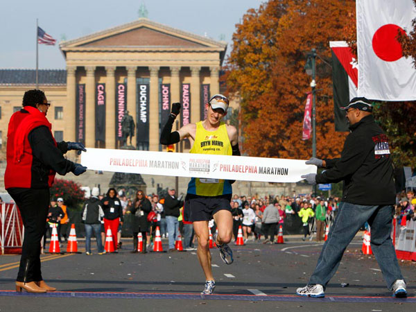 Michael McKeeman, from Ardmore Pa., crosses the finish line, with a time of 2:17:47, as he wins the Philadelphia Marathon, Sunday, Nov. 18, 2012, in Philadelphia.  (AP Photo/ Joseph Kaczmarek)