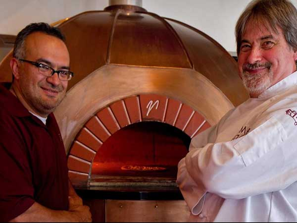 Stalin Bedon (left) and Tom Grim at the oven of Nomad Pizza, May 17, 2012. ( DAVID M WARREN / Staff Photographer )