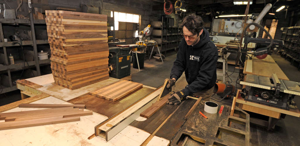 Conlon uses a table saw to cut wood into strips to be glued together and made into cutting and cheese boards at Philadelphia Custom Block & Board Corp. Chef John Brandt-Lee bought the business last year.