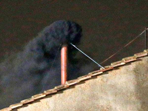 Smoke emerges from the chimney on the roof of the Sistine Chapel, in St. Peter´s Square at the Vatican, Tuesday, March 12, 2013. The black smoke indicates that the new pope has not been elected by the cardinals in conclave. (AP Photo/Michael Sohn)