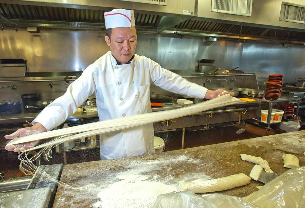 Chef Zeng Feng Zhang works the noodles in the kitchen of the new Nan Zhou<br />Hand Drawn Noodle House, its seating capacity more than doubled.