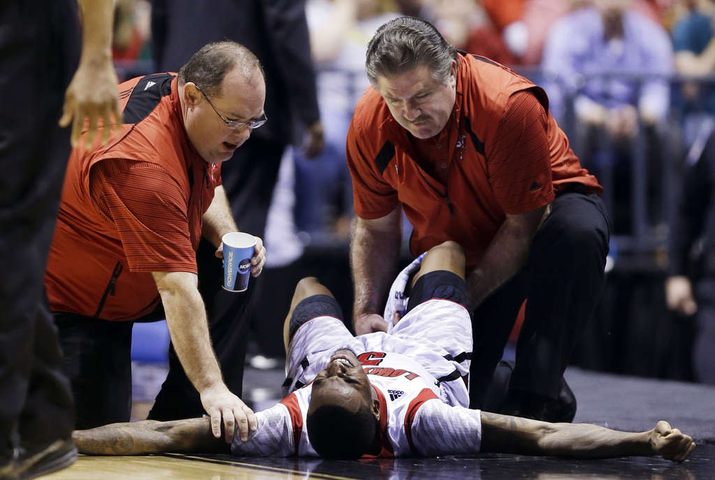 University of Louisville basketball player Kevin Ware writhes in pain after breaking his right leg in 2013 Elite Eight against Duke.