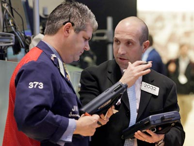 Traders consult Thursday on the floor of the New York Stock Exchange. Stocks edged lower Monday after an industry group reported that U.S. manufacturing growth cooled in March and was weaker than forecast. (AP Photo, File/Richard Drew)