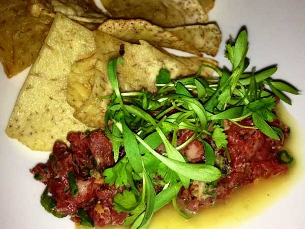 Beef Tartar with bone marrow vinaigrette, crispy shallots, scallion and taro chips.