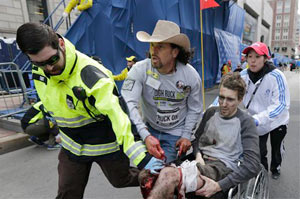 In this April 15, 2013 file photo, an emergency responder and volunteers, including Carlos Arredondo, in the cowboy hat, push Jeff Bauman in a wheel chair after he was injured in an explosion near the finish line of the Boston Marathon.  (AP Photo / Charles Krupa, File)