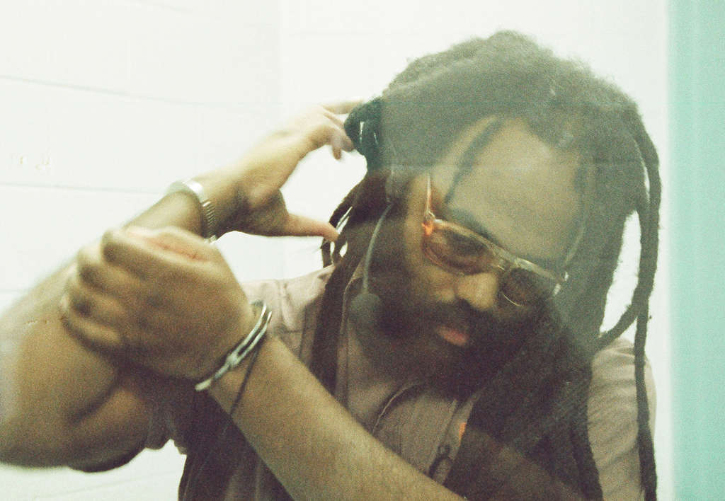 A shackled Mumia Abu-Jamal is photographed through Plexiglasin the isolated visiting room at the super-max prison SCI Greenein Waynesburg, Pa., as seen in the movie.