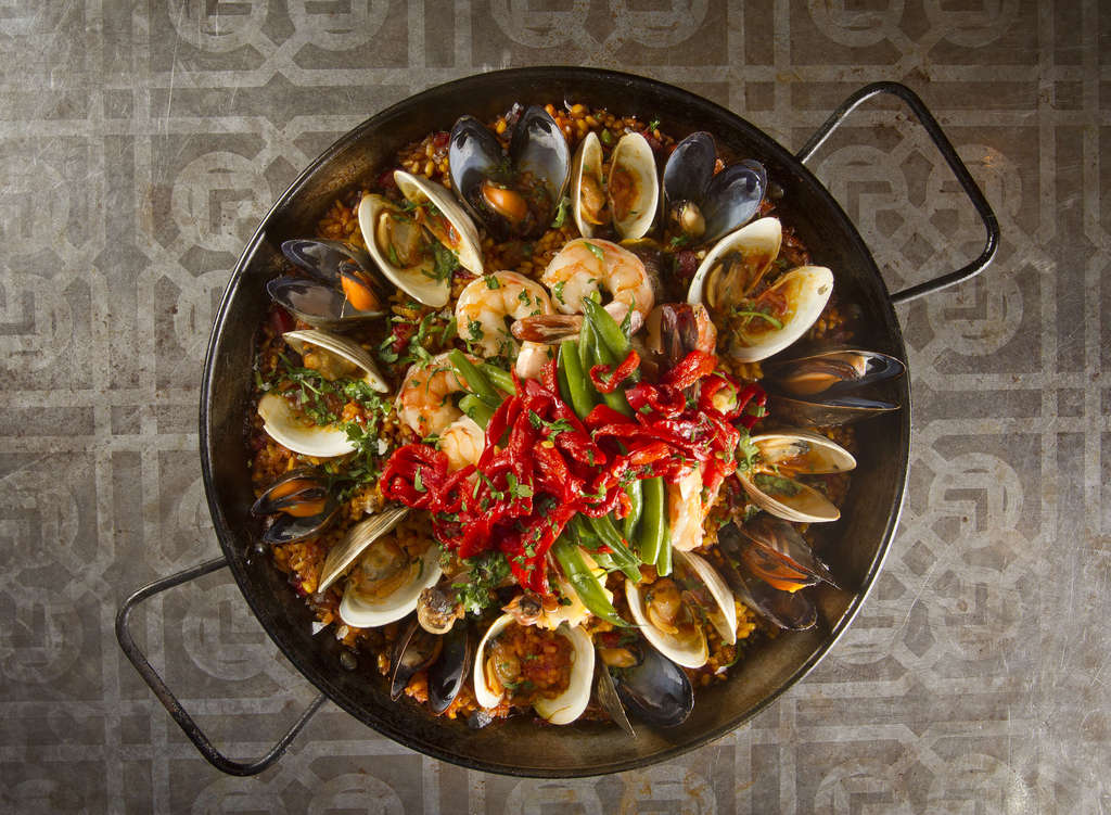A pan of paella Valenciana , with toothsome Calasparra rice and perfectly cooked mussels, clams, shrimp, chorizo, and chicken.