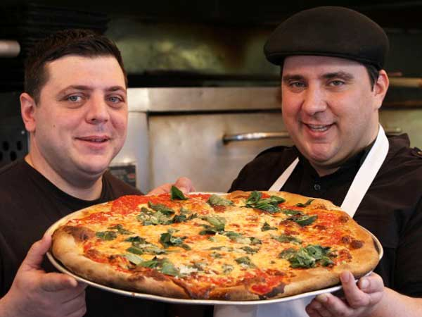 "Cousins Francis Garcia and Sal Basille with their stock in trade on ""PIzza Cuz."""