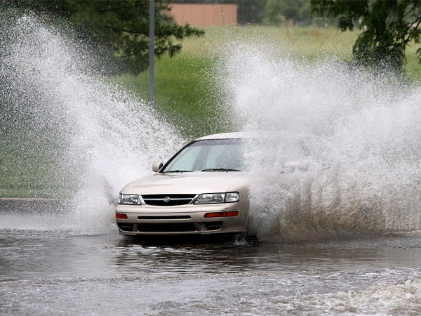 Virginia Drive in Fort Washington has long been prone to flooding. The street was flooded in several locations on June 7, but that did not stop this person in a Nissan sedan. (CHARLES FOX / Staff Photographer)