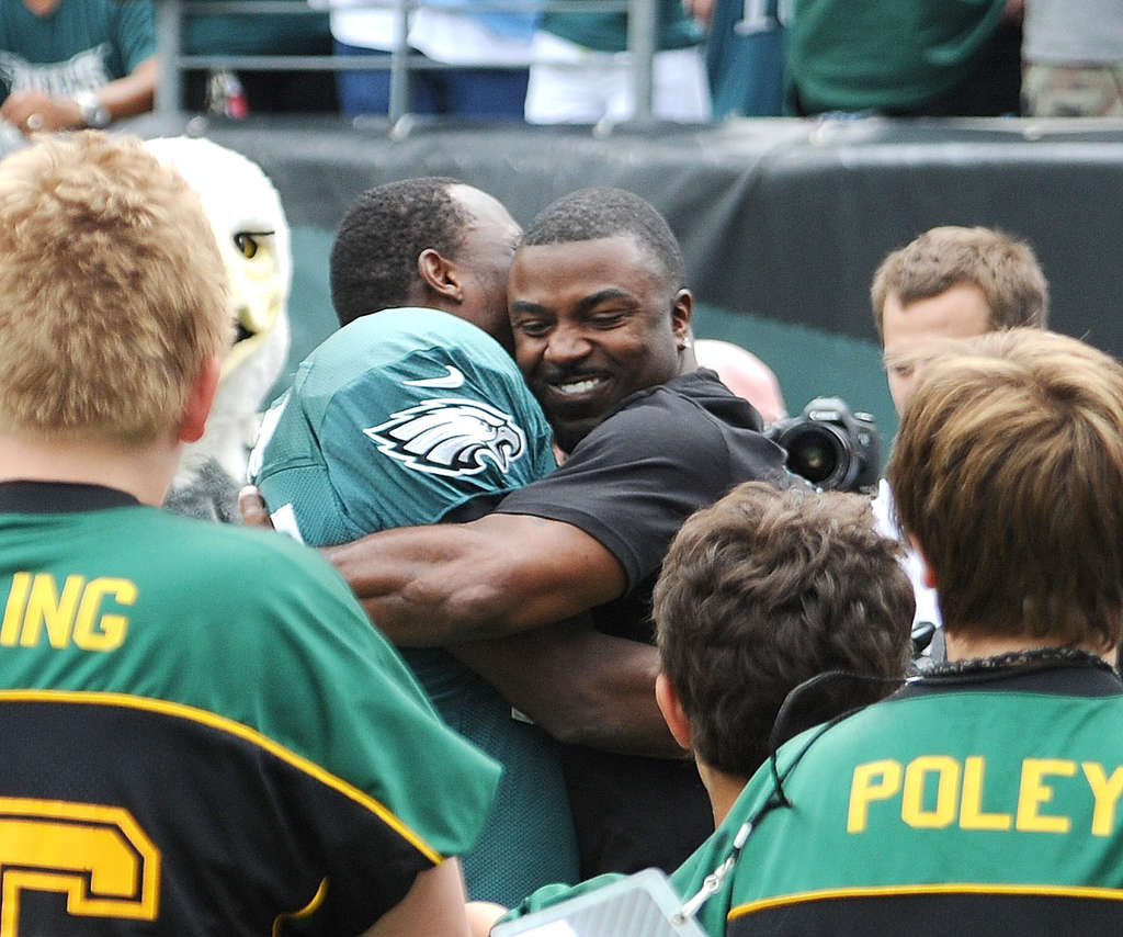 Former Eagles fan favorite Brian Westbrook (right) gives star back LeSean McCoy a bear hug during the introduction of Birds alumni at training camp.