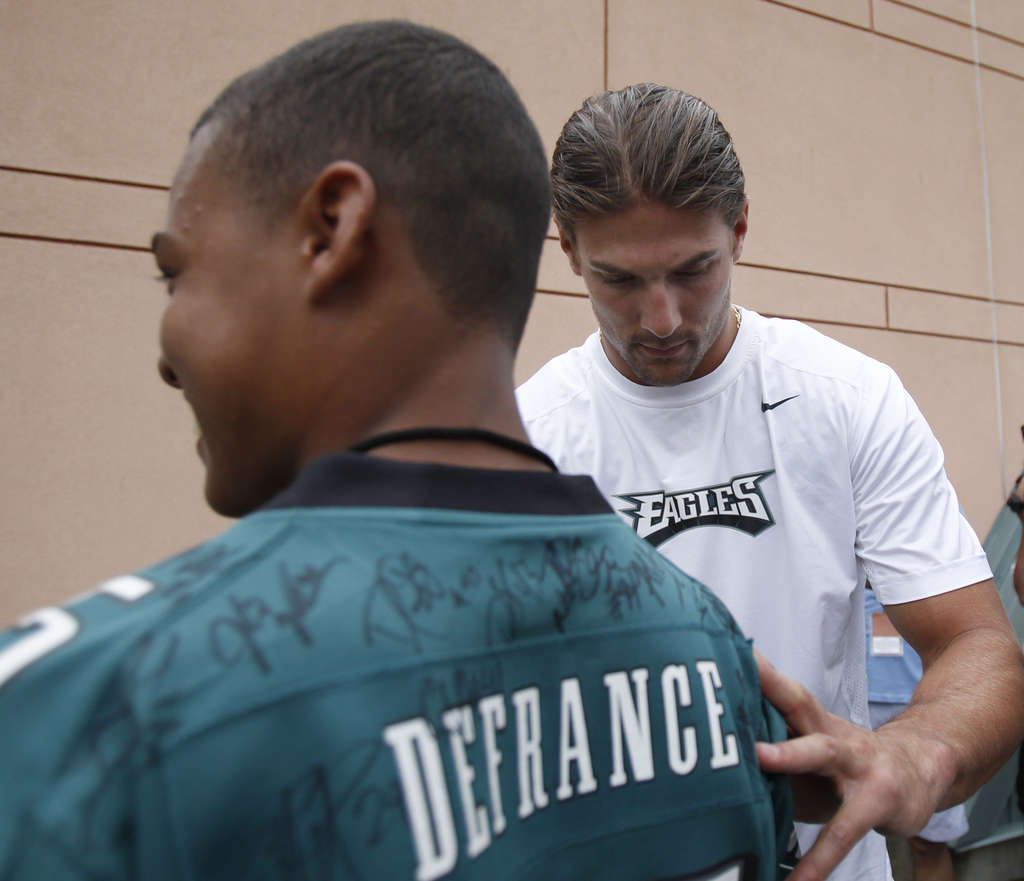 Riley Cooper, back in training camp, signs an autograph for Eagles fan Taj DeFrance.