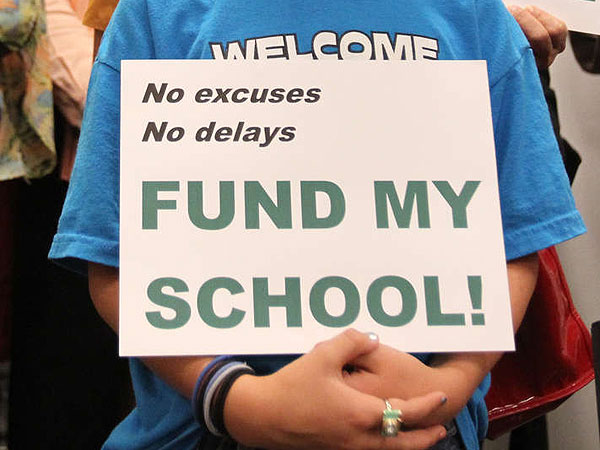 Taryn Flaherty holds a sign urging funds for school while in a jammed room for an Aug. 2013 news conference. The school district´s budget, released this morning, indicates the district needs millions in new money just to maintain current services for the next school year and that more layoffs are likely if that money doesn´t come. ( CHARLES FOX / Staff Photographer )