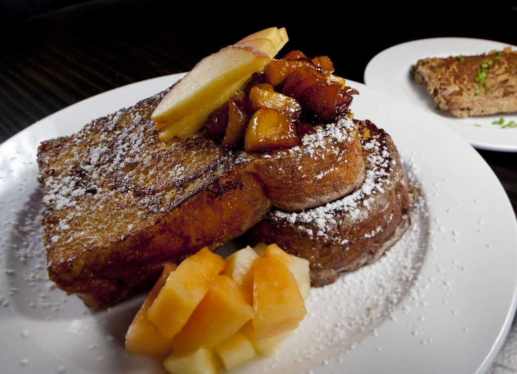 At brunch, the French toast is stuffed with peach-sweetened cream cheese, sprinkled with powdered sugar, and accompanied by fruit.