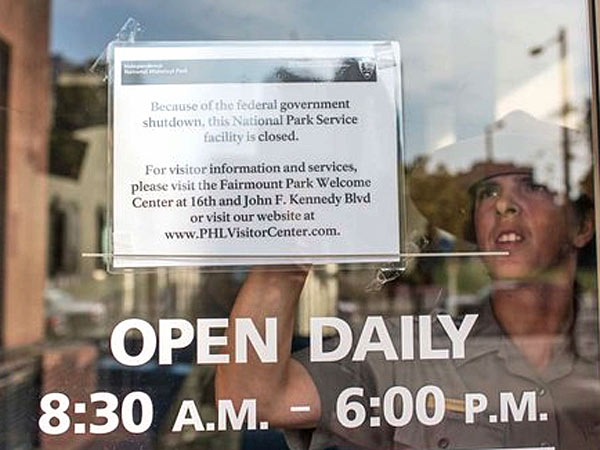 Park ranger Terry Papavasilis puts up a sign informing visitors that the Independence Visitor Center was closed due to the federal government shutdown on Oct. 1, 2013. (Colin Kerrigan / Philly.com)